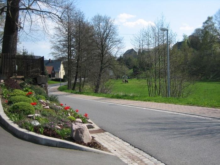Neu gebaute Straßen mit Fußwegen und gepflegte Grundstücke bestimmen das Ortsbild.